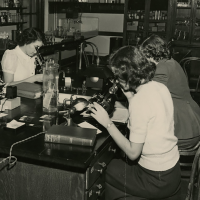 Vintage image of CMU students looking into microscopes.