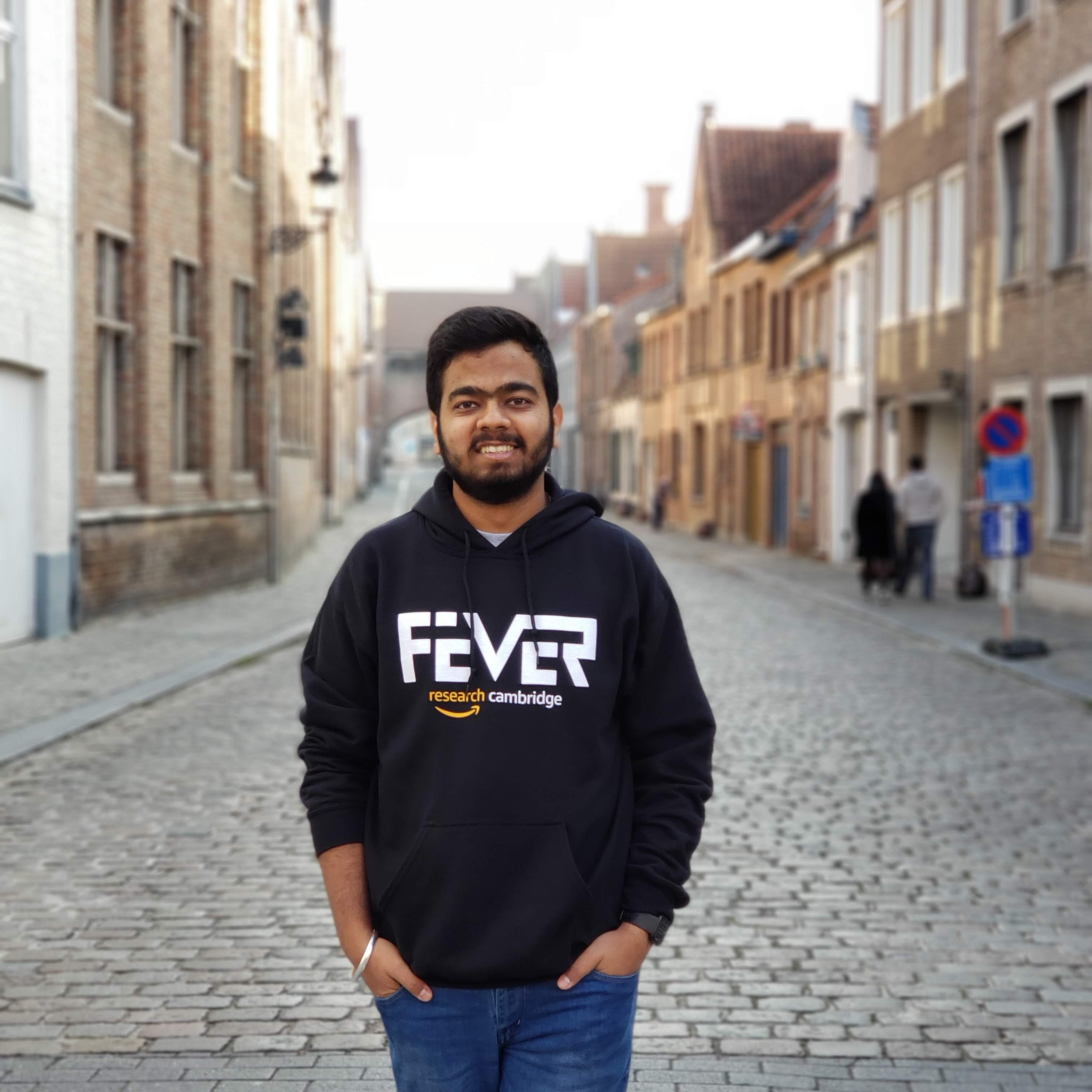Divyansh stands smiling in front of buildings