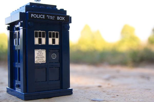 The TARDIS (the Doctor's mode of travel in Doctor Who) sits in the foreground of the image.